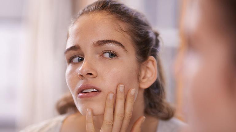 Thói quen sờ tay lên mặt là một trong những nguyên nhân khiến mụn bọc bị chai